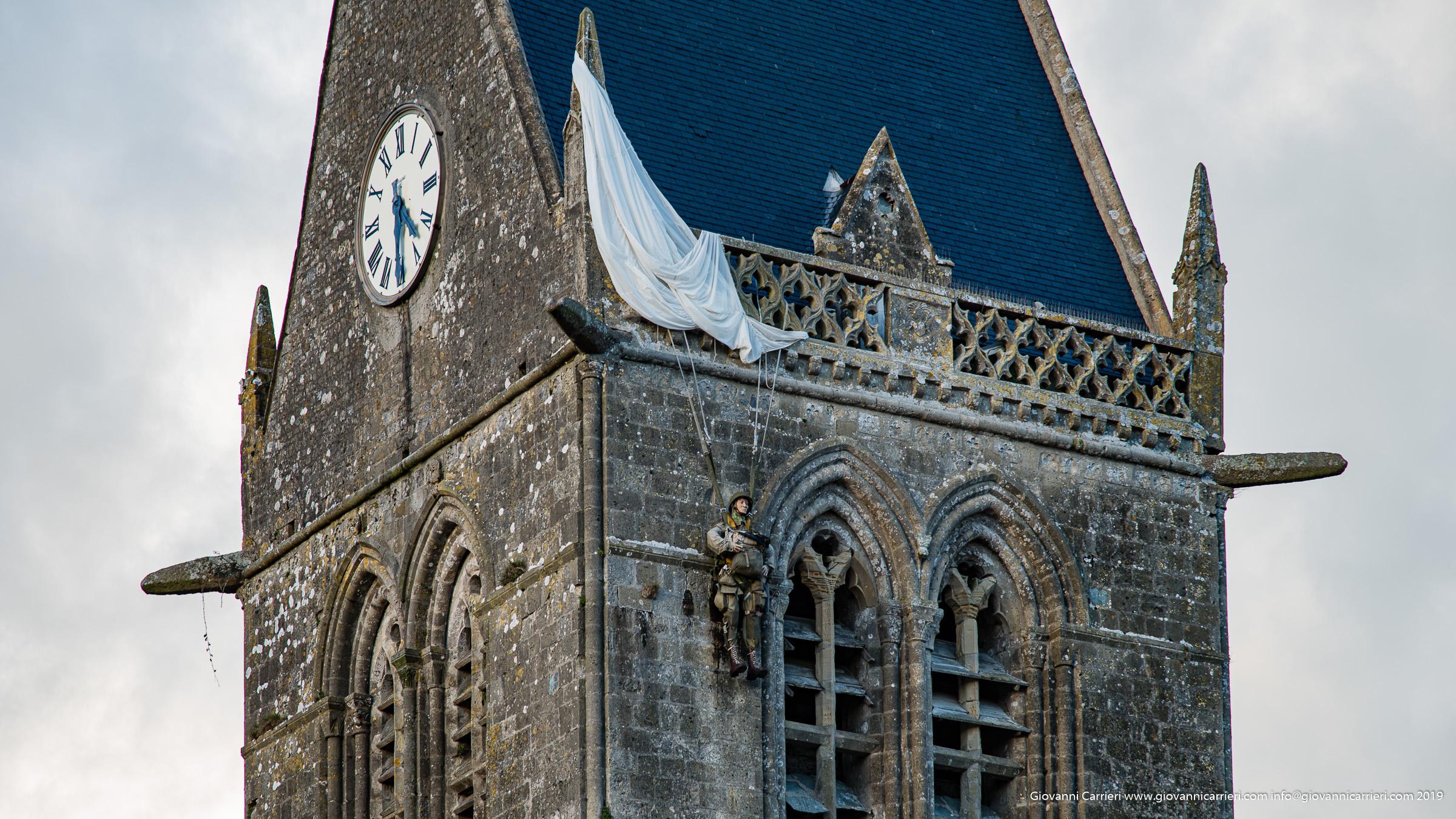 Il campanile della chiesa, con il monumento al paracadutista a Sainte Mère Église