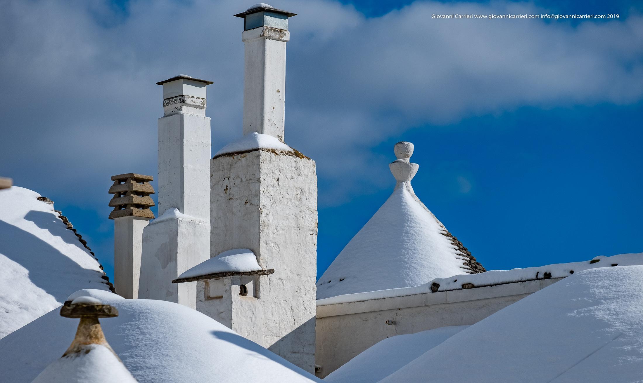 I coni ed i camini innevati dei Trulli di Alberobello