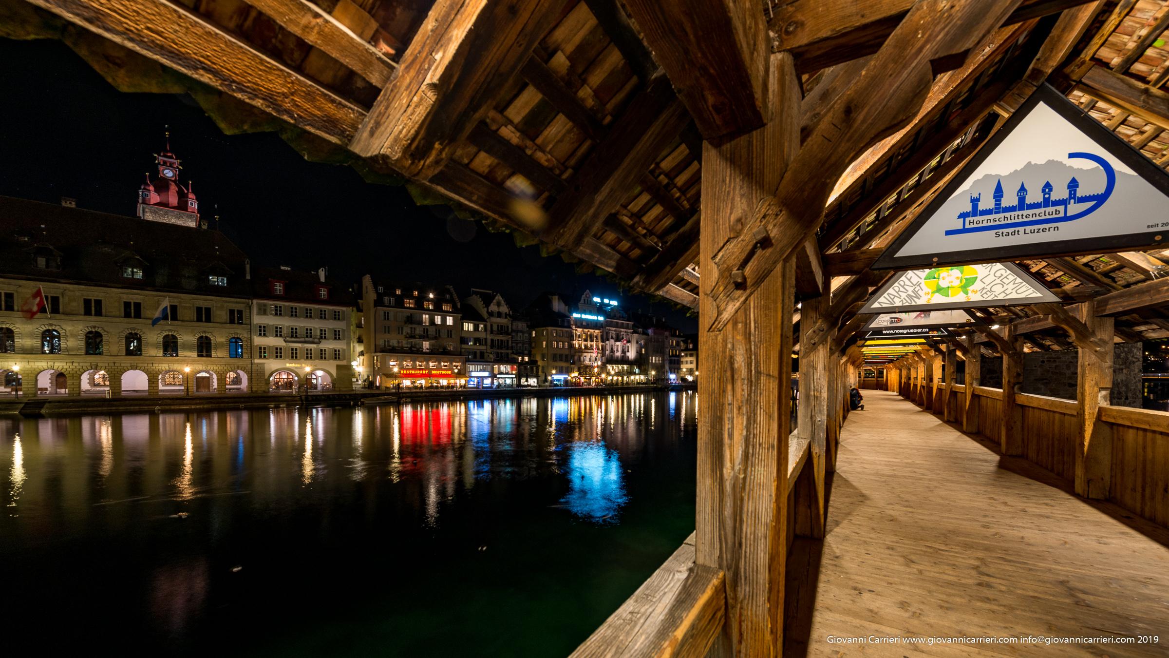 Vista notturna dall'interno del ponte Kapellbrücke del fiume Reuss e dell'antica città di Lucerna