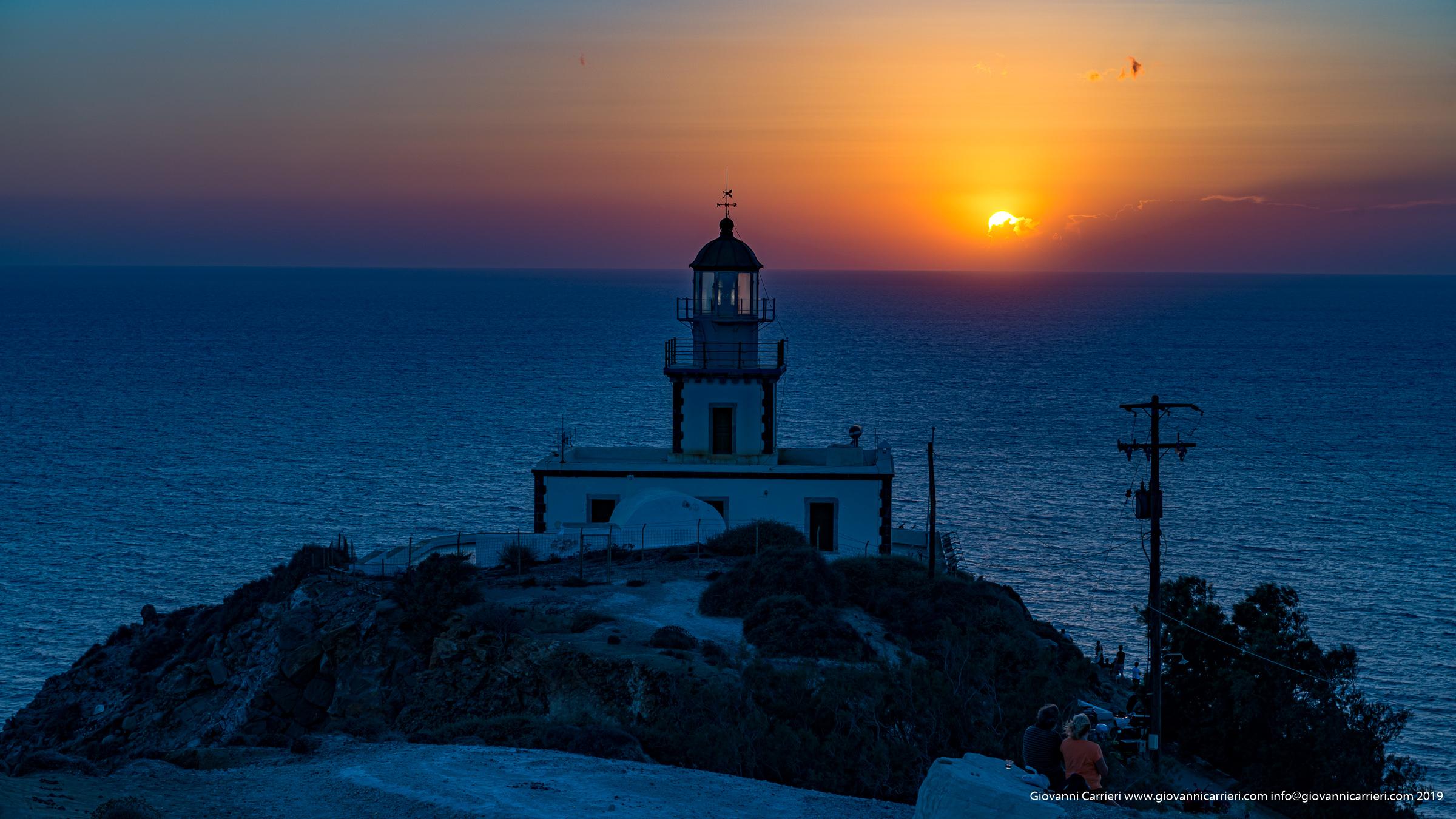 Il tramonto abbaglia il faro di Santorini